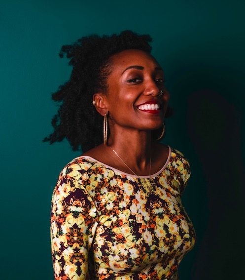 Rebecca KellyG smiling at the camera. She is wearing a yellow floral top and gold hoop earrings and standing in front of a dark green background.