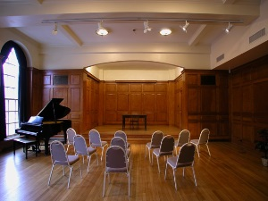 A spacious, wood-paneled performance hall with large arched windows against the left wall. Chairs are set up in rows facing a small stage, with a grand piano in front of the windows.