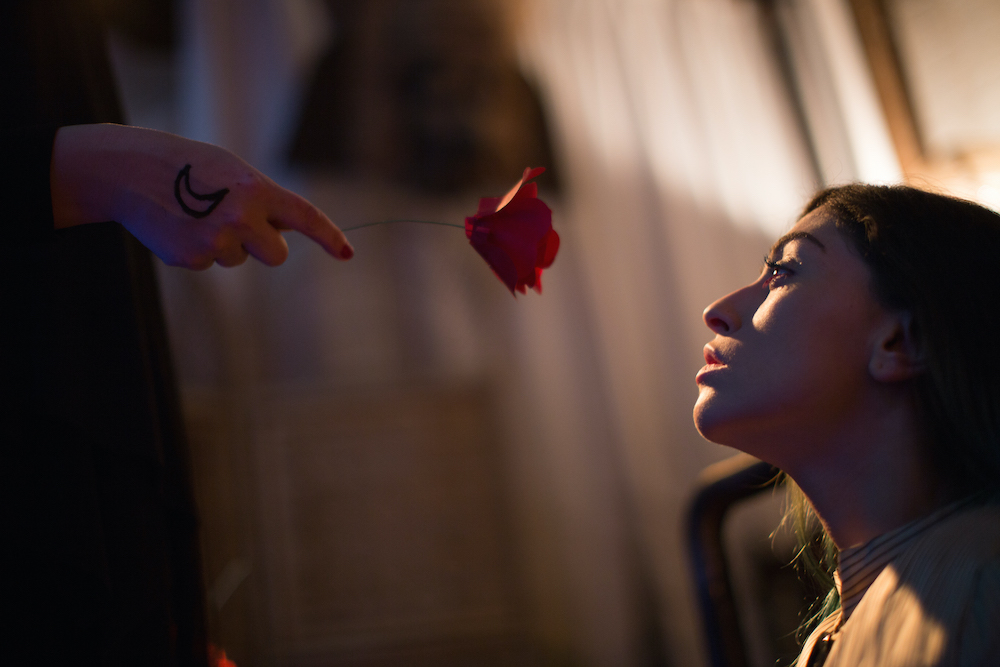 Production photo of a hand with a crescent moon tattoo holding a red rose towards the face of a woman with brown hair