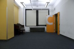 A mid-sized carpeted room with yellow and white walls. A piano sits next to some large windows.